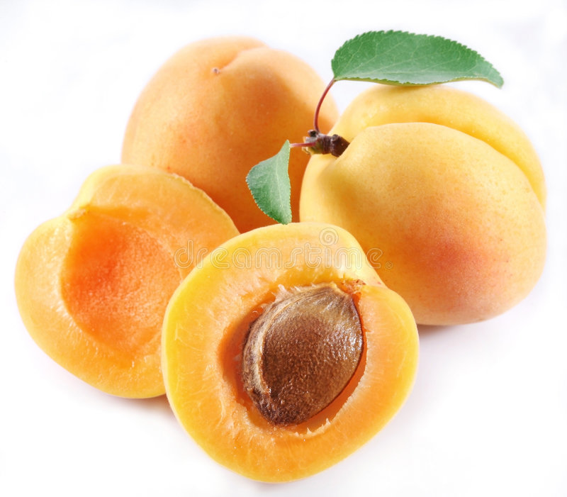 Apricot. Whole and the halves of apricot lie on a white background stock image