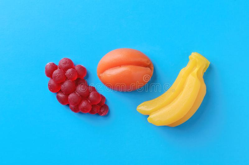 Apricot, berries and banana sweet marmalade candy on blue background. Top view. Trendy colorful photo. Minimal style with colorful paper backdrop. Flat lay royalty free stock image