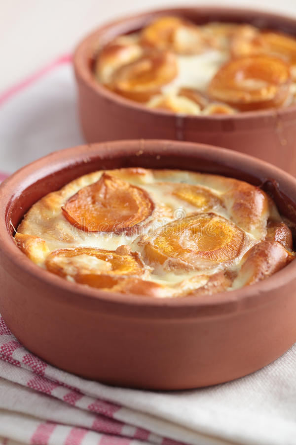 Apricot clafoutis. Clafoutis with apricot in baking dishes stock photo