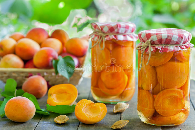 Apricot compote. With fresh apricots in the basket royalty free stock photography
