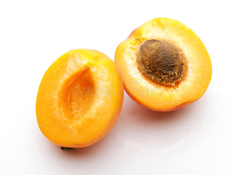 Apricot cutting in half with stone close-up. On white background stock photography