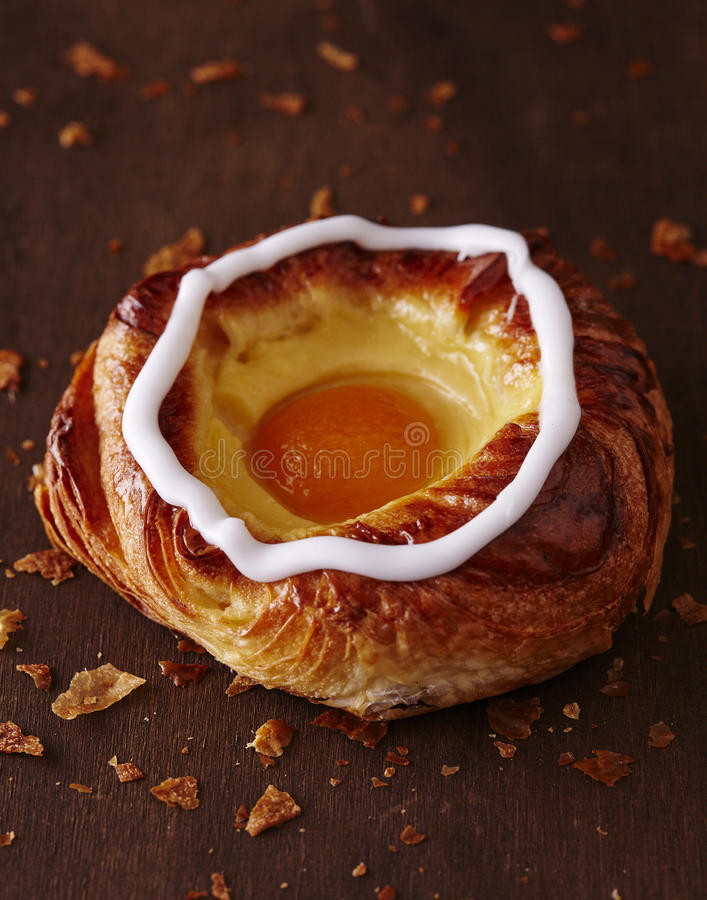 Apricot Danish. With crumbs on dark wooden board stock images