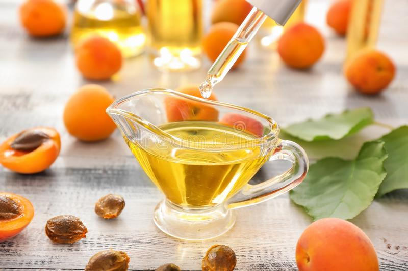 Apricot essential oil dripping into gravy boat on wooden table royalty free stock image