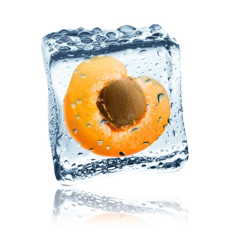 Apricot frozen in ice cube, isolated. Ripe sweet apricot half with stone frozen inside transparent ice cube, covered with water drops, isolated on white royalty free stock photography