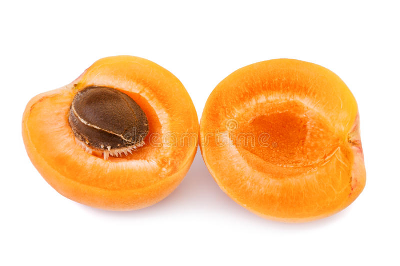 Apricot fruit half. Two halves of apricot isolated on white. Apricot with fruit kernel on white background. Closeup stock photography