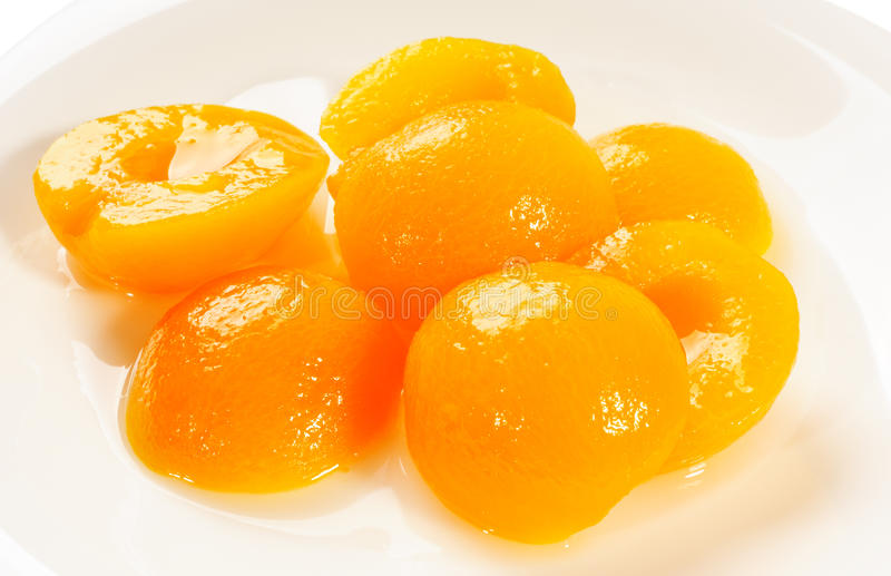 Apricot halves. Apricot peeled halves with sugar syrup on plate, above view, isolated on white stock photo