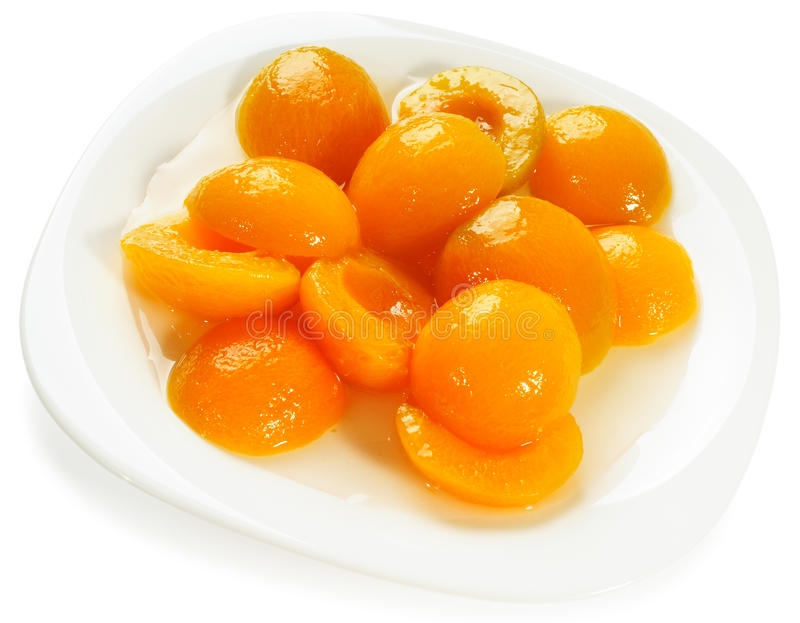 Apricot halves on plate. Apricot peeled halves with sugar syrup on plate over white background stock images