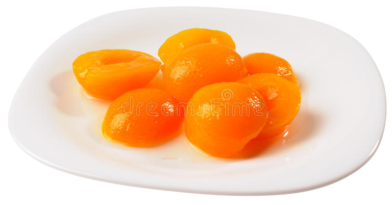 Apricot halves on plate isolated. Apricot peeled halves with sugar syrup on plate isolated on the white stock image