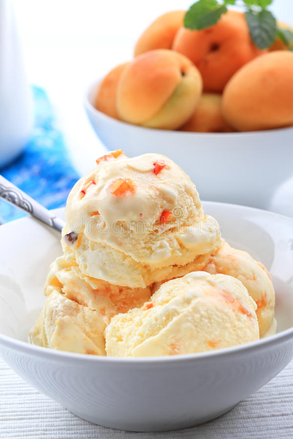 Apricot ice cream. Delicious bowl of apricot ice cream with fresh fruits royalty free stock photography