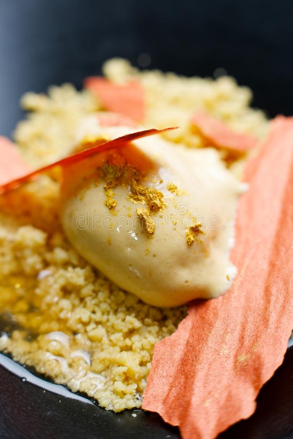 Apricot ice cream. With elderberry in a black bowl royalty free stock image