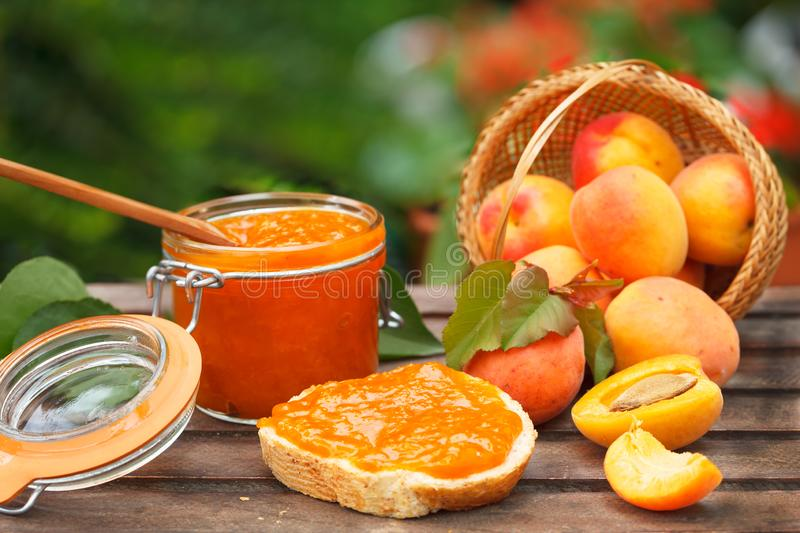 Apricot jam in a glass jar, fresh apricots in a basket on wooden background royalty free stock photos