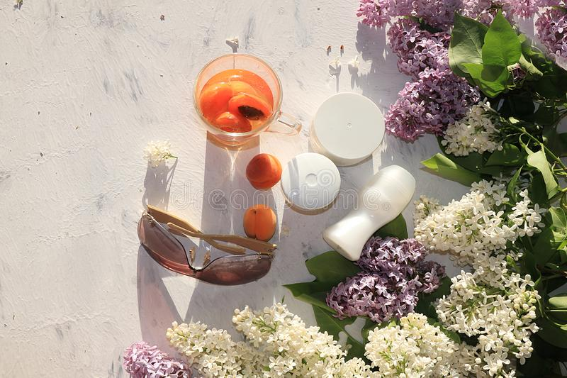 Apricot juice, apricots, on a sunny table next to creams for body care and deodorant, preparing for a summer holiday in the sun, c. Opy space, top view. Summer stock photo