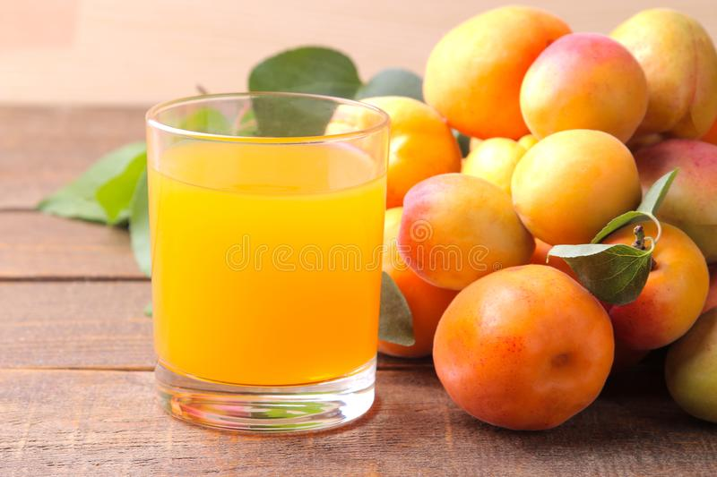 Apricot juice next to fresh apricots on a brown wooden background royalty free stock images
