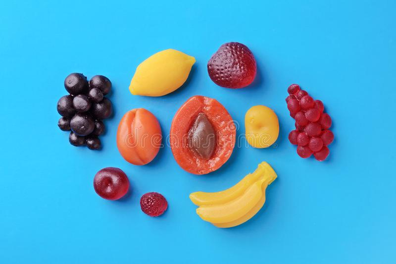 Apricot, lemon, berries and banana sweet candy on blue background. Apricot, lemon, banana, strawberry, cherry, raspberry and berries sweet marmalade candy on royalty free stock image