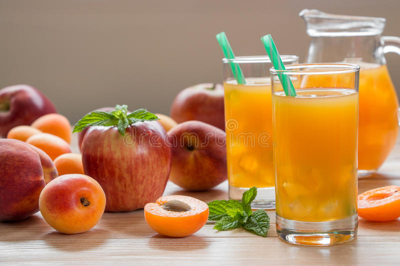 Apricot peach apple juice with ice. Apricot peach apple juice in glasses with ice near the jar of juice and scattered apricots, peaches, apple, mint on a light royalty free stock image