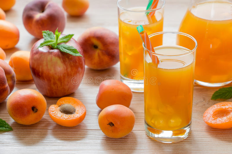 Apricot peach apple juice with ice. Apricot peach apple juice in glasses with ice near the jar of juice and scattered apricots, peaches, apple, mint on a light royalty free stock photos