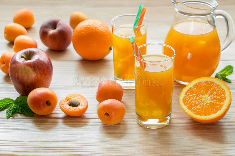 Apricot peach apple orange juice with ice. Right fruit juice in glasses with ice near the jar of juice and scattered apricots, peaches, apple, orange left empty stock photos