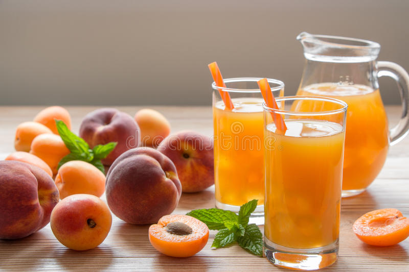 Apricot and peach juice with ice. Apricot and peach juice in glasses with ice near the jar of juice and scattered apricots and peaches, mint on a light wooden royalty free stock images