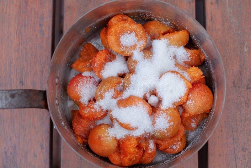 Apricotes lumineux couvrant le sucre se préparant à la confiture faite maison photos stock