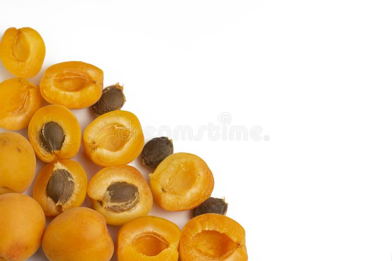 Apricots and cut apricots on a blank white background, arranged on down left corner, with copy space. Top view. royalty free stock photo