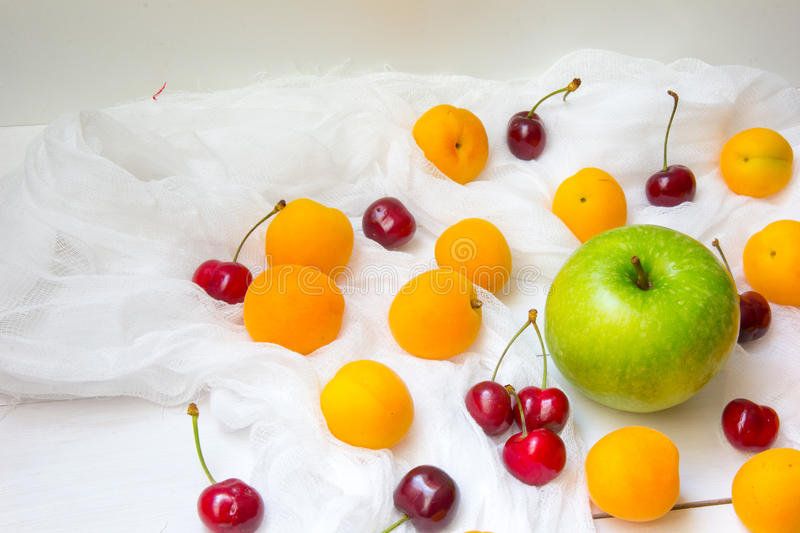 Apricots, green apple and cherry berries at white background stock image