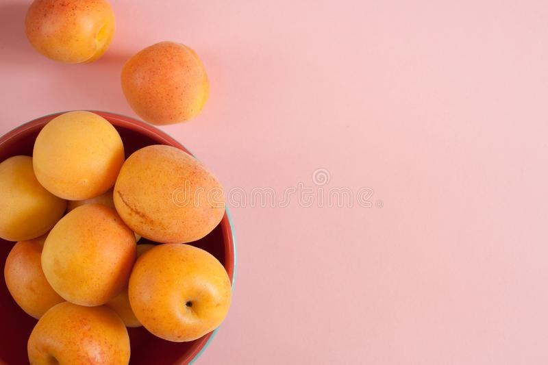 Apricots in round terracotta bowl and near it on pink pastel background. royalty free stock photo
