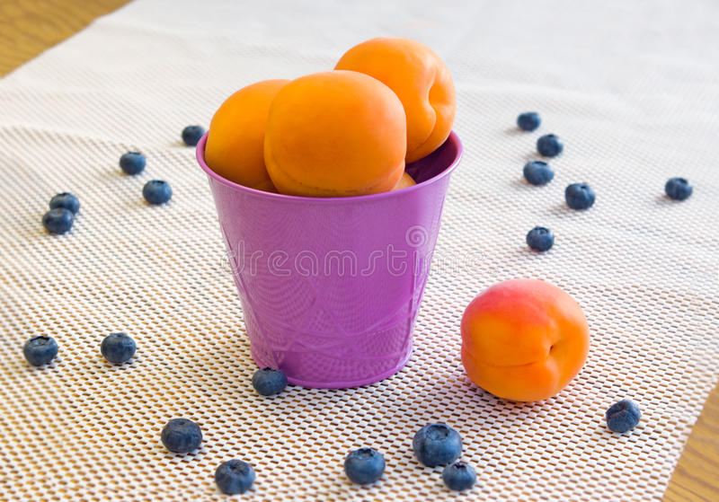 Apricots in a violet bucket and blueberries on a white background. Delicious summer yellow apricots in a violet bucket with blueberries on a white background royalty free stock photography