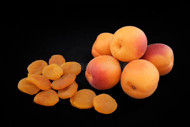Apricots of yellow color and dried apricots on a black background royalty free stock images