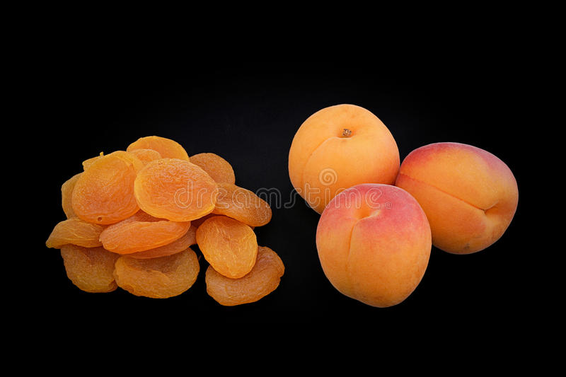 Apricots of yellow color and dried apricots on a black background (closeup) stock images