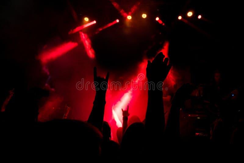 Apriete en un concierto de rock, los cuernos de metales pesados de la roca firman adentro la niebla de un partido fotografía de archivo
