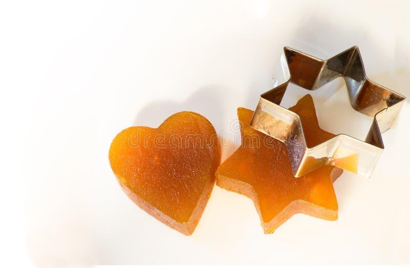 Aprikons för gelé för kanderad frukt i form av hjärta och stjärnan av David med järn bildar royaltyfri fotografi