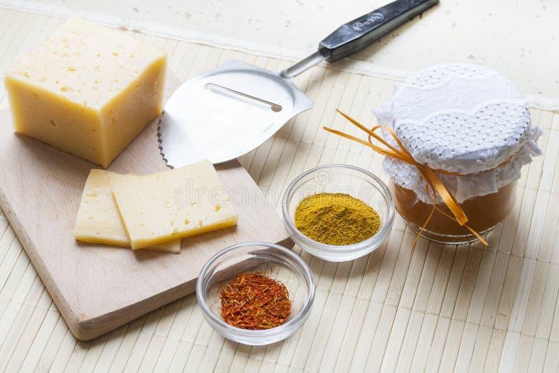 Aprikoscurry i en glass bunke, en ost, kryddor och nya aprikors royaltyfri bild