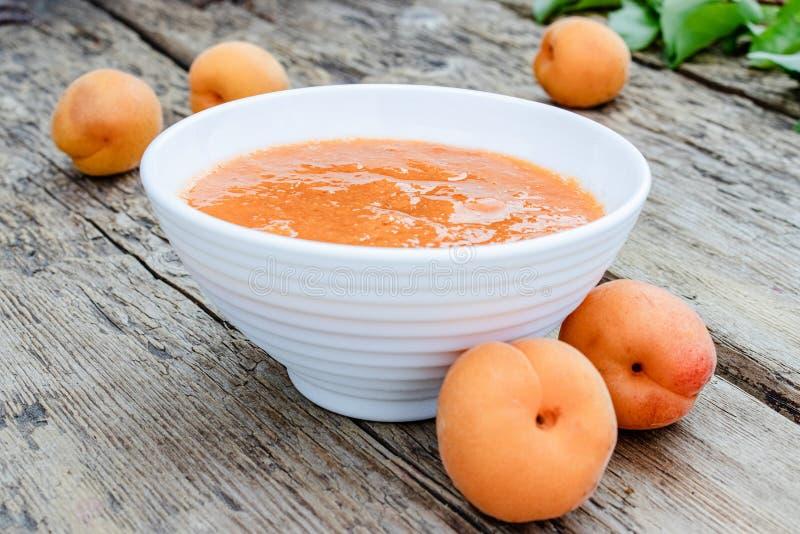 Aprikosdriftstopp i en vit bunke och mogna aprikors på en trätabell royaltyfri foto