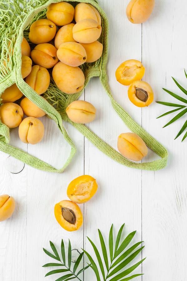Aprikosen in einem Einkaufsnetz und in den Grünblättern auf einem weißen Brett stockfotografie