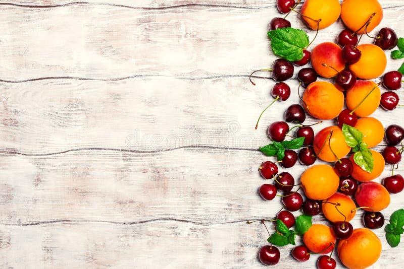 Aprikosen und Kirschen auf rustikalem Hintergrund lizenzfreies stockbild