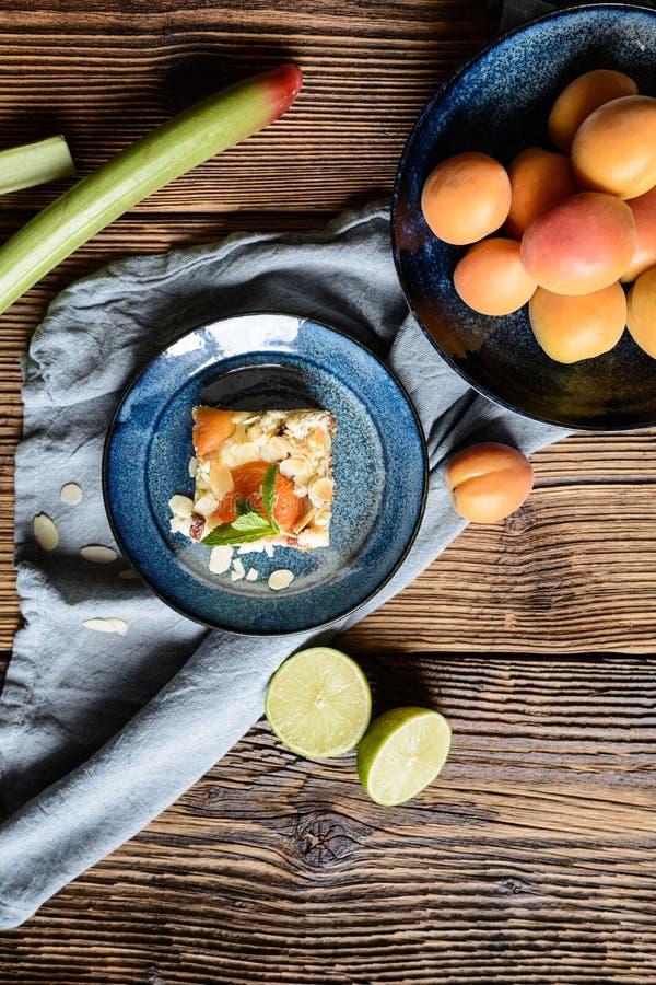 Aprikosenkäsekuchen mit dem Rhabarber, überstiegen mit Krümel- und Mandelflocken lizenzfreie stockfotografie