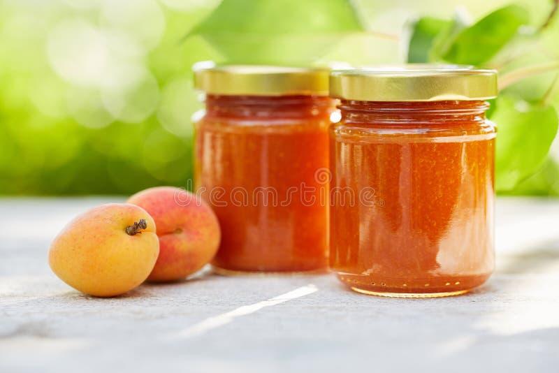 Aprikosenmarmelade in den Glasgefäßen auf einem Holztisch stockfotografie