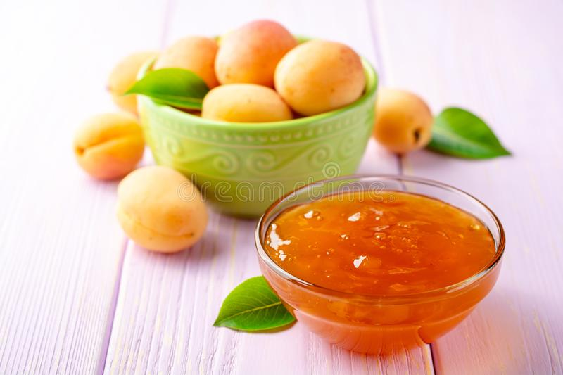 Aprikosenmarmelade in der Glasschüssel und in den frischen Aprikosen auf hellpurpurnem hölzernem Hintergrund stockbild