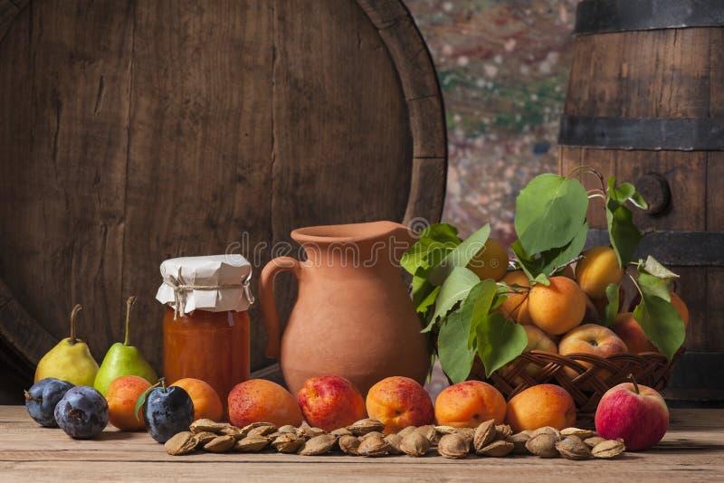 Aprikosenmarmelade, frische Frucht und ein hölzernes Fass lizenzfreie stockbilder