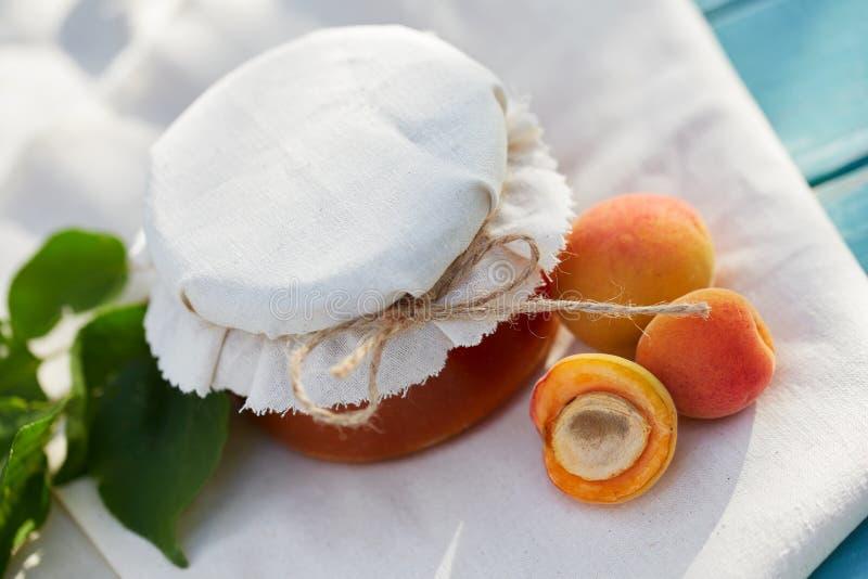 Aprikosenmarmelade im Glasgefäß mit frischer Frucht stockfotografie