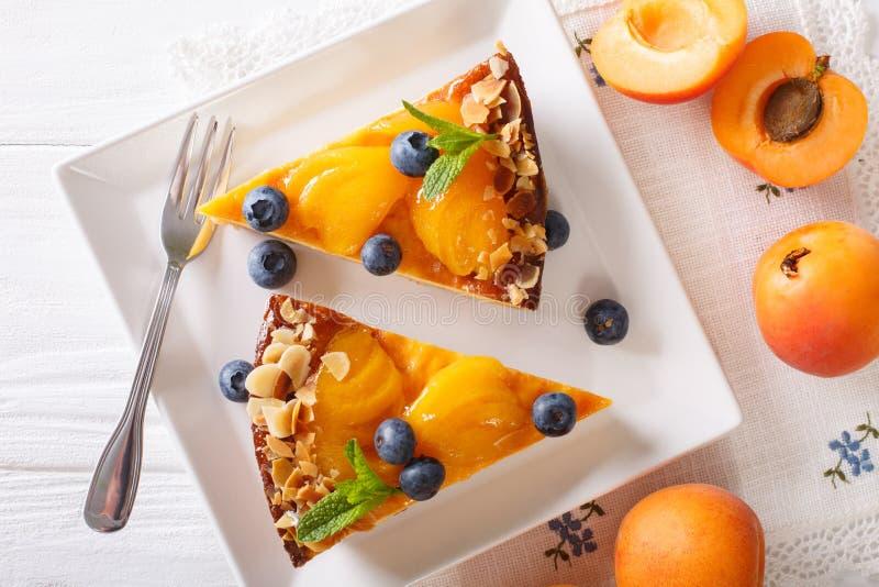Aprikosentorte mit Blaubeeren und nuts Nahaufnahme auf einer Platte Horiz lizenzfreies stockfoto