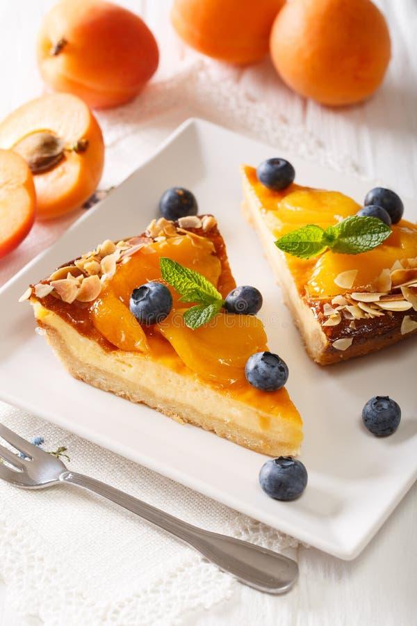 Aprikosentorte mit Blaubeeren und nuts Nahaufnahme vertikal stockbild