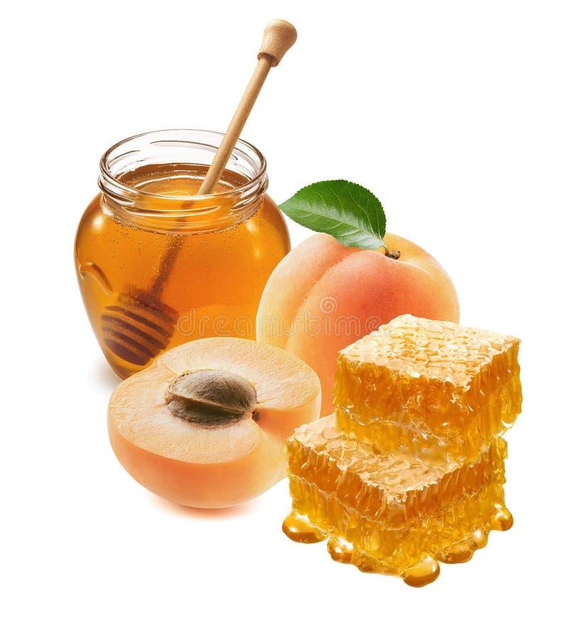 Aprikoser, honungsburkar med en dipper och en bikaka som är isolerad på vit bakgrund royaltyfri bild