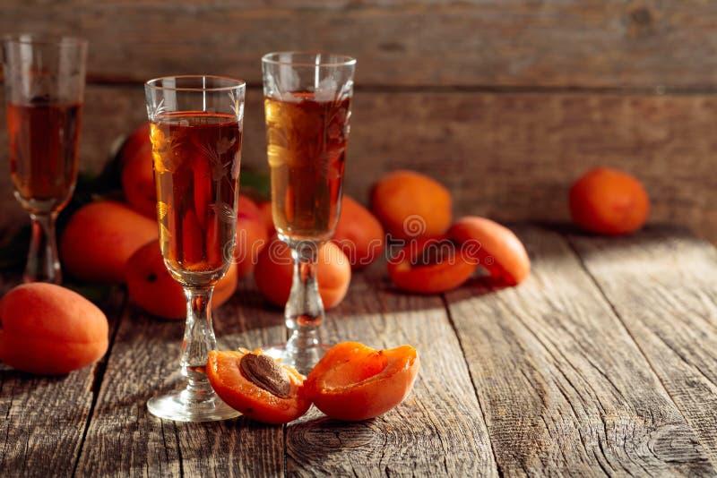 Aprikosstarksprit och nya aprikors på en gammal trätabell royaltyfri foto