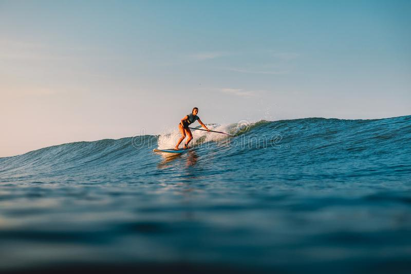 April 12, 2019. Bali, Indonesia. Stand Up Paddle surfer ride on ocean wave. Stand Up Paddle surfing at waves in Bali stock photography