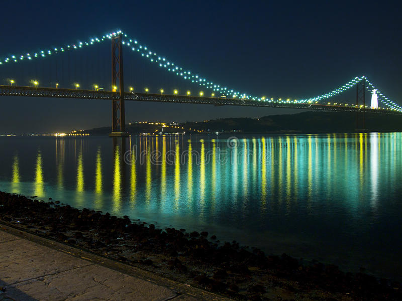 April 25 Bridge In Lisbon. Night view of the April 25 (25 de Abril) Bridge in Lisbon, Portugal as seen from the Belem district. Completed in 1966 , this stock photos