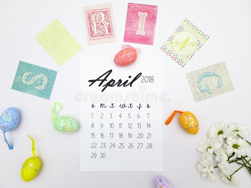 April 2018 calendar, Easter eggs and white chrysanthemums on a white background royalty free stock photo