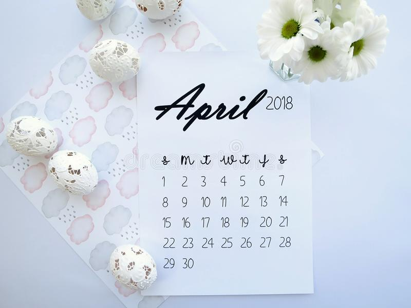 April 2018 calendar, Easter eggs and white flowers stock photography