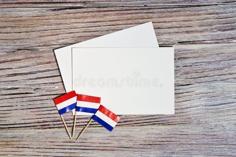 30. April drei Miniflaggen mit zwei Blättern Weißbuch Das Konzept des Unabhängigkeitstags der Niederlande und des nationalen stockfotografie