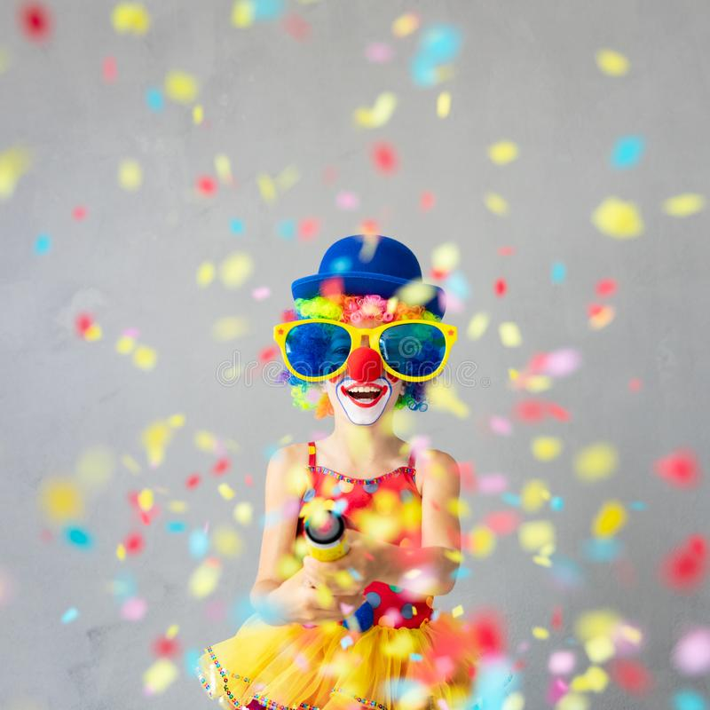 1 April Fool`s Day Concept. Funny kid clown with party poppers. Happy child playing at home. 1 April Fool`s day concept royalty free stock photography